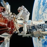 An astronaut makes adjustments to the Hubble space telescope. In the next photo, see what it's like to hover above planetary clouds. Image Credit: World Perspectives/Getty Images